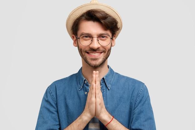 Портрет привлекательного бородатого мужчины с очаровательной улыбкой, щетиной, сложенными ладонями, радостно смотрит, верит в удачу