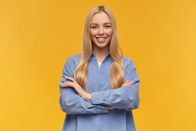 金髪の長い髪の魅力的な、美しい少女の肖像画。青いシャツを着ています。人と感情の概念。腕を組んで胸に抱きます。オレンジ色の背景の上に分離されたカメラで見て