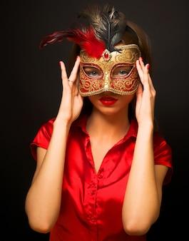 赤い冷たいカーニバルマスクを着て魅力的な美しい若い女性の肖像画