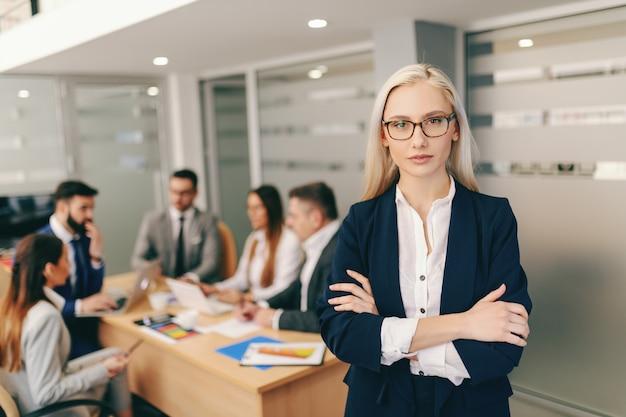 Портрет привлекательной блондинки в деловой одежде, держащей скрещенные руки, стоя в зале заседаний
