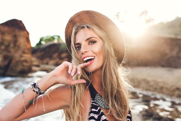 夕日を背景に岩のビーチでポーズをとって長い髪を持つ魅力的なブロンドの女の子の肖像画。彼女は唇に指を当て、カメラを見つめます。