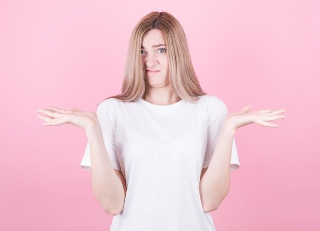 Портрет привлекательной блондинки в белой рубашке, показывающей, что я не знаю, жест изолирован на розовой стене