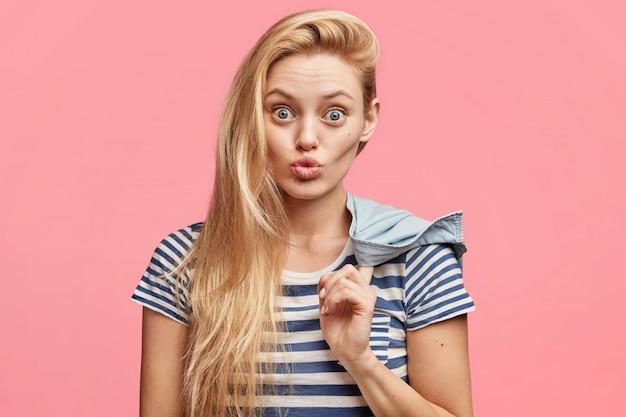 유쾌한 외모를 가진 매력적인 금발의 젊은 여자의 초상화, 스트라이프 티셔츠를 입고 둥근 입술을 가지고 카메라를 쳐다보고 찡그린 얼굴을합니다.