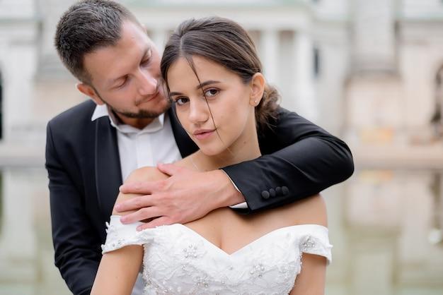 魅力的なブルネットの花嫁とハンサムな新郎の肖像画