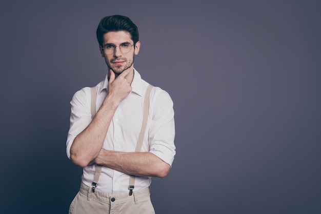 あごに腕を持っている魅力的なビジネスマンの魅力的な外観の肖像画心の深い服を着た正装白いシャツベージュのサスペンダーの仕様。