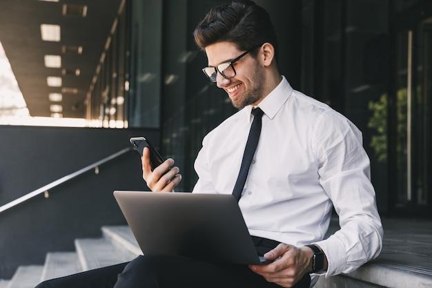 ノートパソコンでガラスの建物の外に座って、スマートフォンを保持しているフォーマルなスーツに身を包んだ魅力的なビジネスマンの肖像画