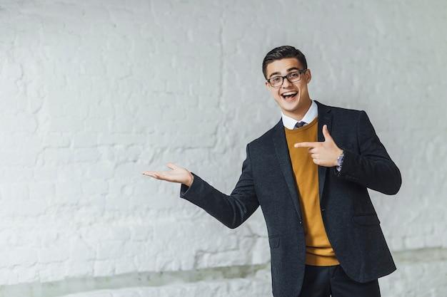 Портрет привлекательного бизнесмена, показывающего хорошо, одетого в желтый свитер и черный пиджак.