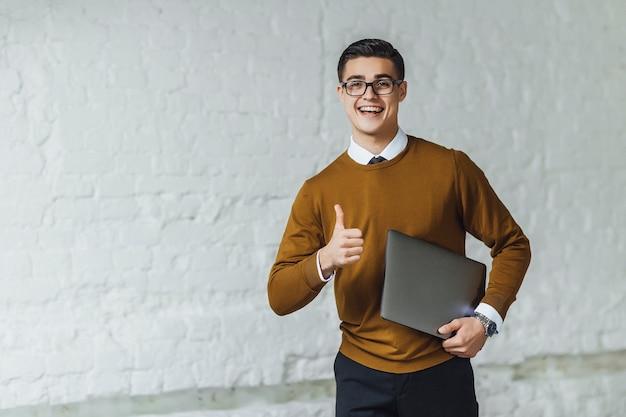 Портрет привлекательного бизнесмена, жестикулирующего хорошо знаком, в желтом свитере