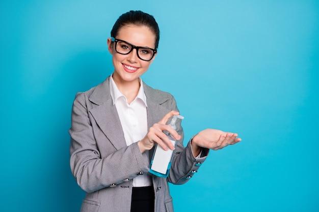 明るい青色の背景で分離された抗菌安全な化学石鹸ストップインフルエンザを使用して魅力的なカジュアルで陽気な女性の肖像画