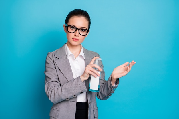 明るい青色の背景に分離された抗菌安全な液体石鹸を使用して魅力的なカジュアルコンテンツの女性の肖像画