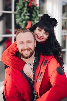 カメラに微笑んで赤で魅力的な白人カップルの肖像画。バックグラウンドでぼやけたクリスマスリース。