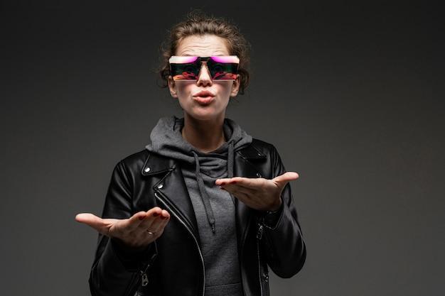 Портрет привлекательной кавказской девушки в стильных очках, серой кофте и черной кожаной куртке удивлен на темно-сером фоне
