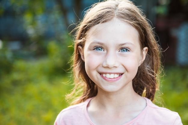 아름 다운 파란 눈을 가진 매력적인 백인 어린 학생 소녀의 초상화. 카메라를 보고 웃는 행복한 아이 - 클로즈업, 야외