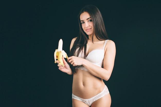 Портрет привлекательной кавказской усмехаясь женщины есть банан.