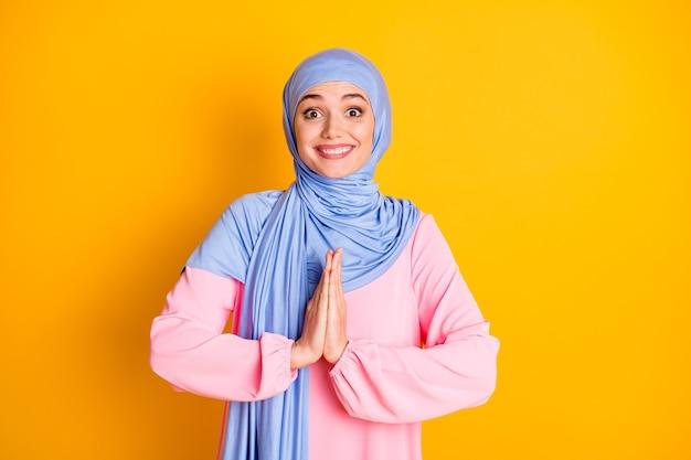 Портрет привлекательной веселой веселой мусульманки в хиджабе с просьбой о подарке-сюрпризе, изолированной на ярко-желтом фоне