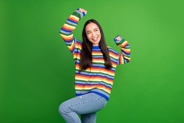 鮮やかな緑の色の背景に分離された楽しい自由時間を楽しんで踊る魅力的な陽気な女の子の肖像画