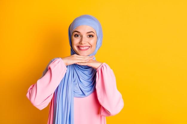 밝은 노란색 배경 위에 고립된 채 파란색 히잡을 쓰고 있는 매력적인 쾌활한 이슬람 여성의 초상화