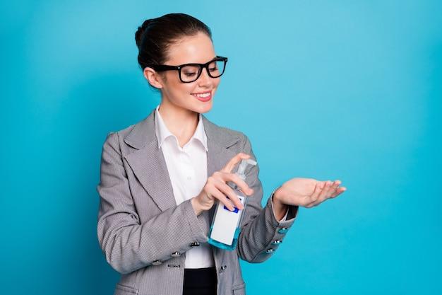 明るい青色の背景で隔離のアルコール抗菌安全スプレークレンジング手を使用して魅力的な陽気な女性の肖像画