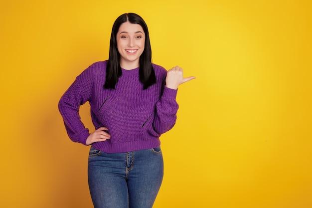 Портрет привлекательной веселой великолепной очаровательной девушки, указывающей пальцем на пустое пространство, изолированное на желтом фоне