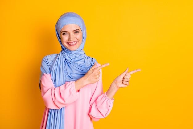 밝은 노란색 배경에 격리된 복사 공간 광고를 보여주는 히잡을 쓴 매력적인 쾌활한 이슬람교도의 초상화