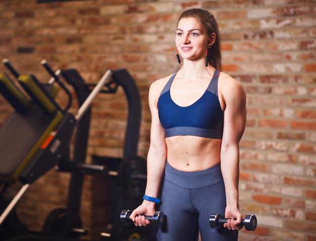 그녀의 귀에 헤드폰으로 매력적인 쾌활 한 sportswoman의 초상화. 벽돌 벽의 배경에 체육관에서 아령으로 운동을하는 스포티 한 여자