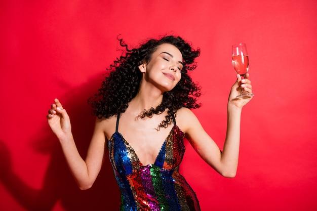 明るい赤色の背景に分離された楽しい娯楽を持ってワインダンスを飲む魅力的な陽気なウェーブのかかった髪の少女の肖像画