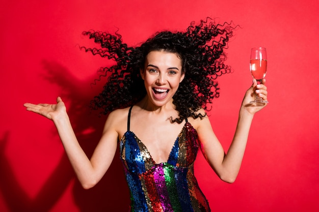 Портрет привлекательной веселой волнистой девушки, пьющей вино, весело проводящей день празднования, изолированной на ярко-красном цветном фоне