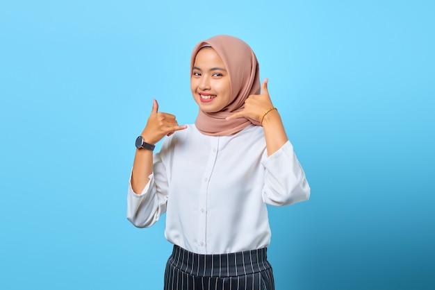 手で電話ジェスチャーをしている魅力的な陽気な若いアジアの女性の肖像画