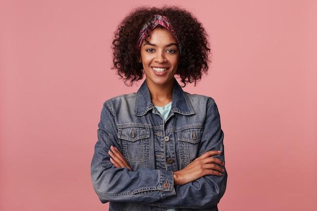 Портрет привлекательной веселой молодой темнокожей женщины с короткой стрижкой, сложив руки на груди и смотрящей с приятной широкой улыбкой, позирующей в повседневной одежде