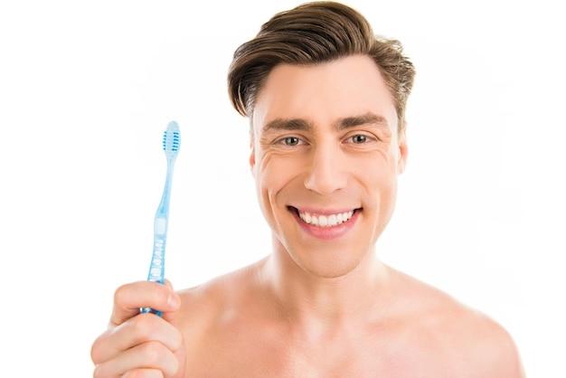 歯ブラシを保持している魅力的な陽気な若い男の肖像画