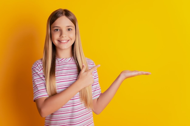 노란색 배경에 손바닥 포인트 손가락 빈 공간 광고를 들고 있는 매력적인 쾌활한 소녀의 초상화