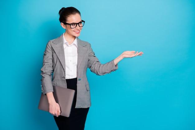手のひらのコピースペースのアドバイスを保持しているラップトップを運ぶ魅力的な上品で陽気な女の子のスペシャリストの肖像画は、明るい青色の背景を分離しました