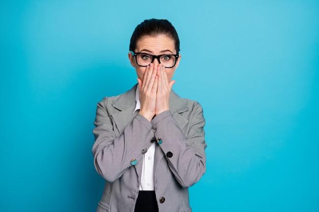 Портрет привлекательной стильной веселой застенчивой скромной бизнес-леди, закрывающей лицо, изолированной на ярко-синем цветном фоне