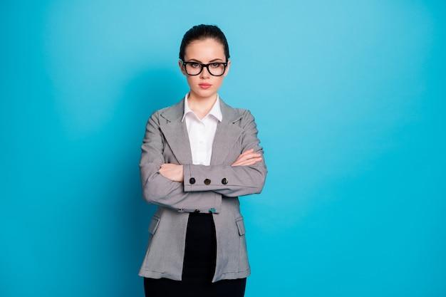 매력적인 고급 콘텐츠 진지한 여성 코치의 초상화는 생생한 파란색 배경 위에 격리된 팔짱을 끼고 있습니다.