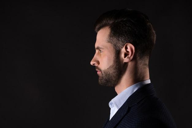Портрет привлекательного стильного мужчины в куртке, изолированной на темно-черном цветном фоне