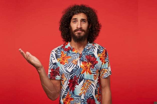 Портрет привлекательного растерянного бородатого парня с кудрями, недоуменно смотрящего в камеру с поднятой ладонью, в разноцветной рубашке с цветами, позирующего на красном фоне