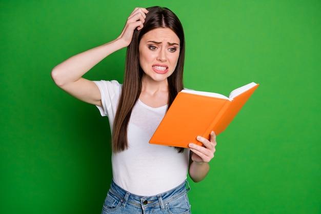 魅力的な混乱した知的少女オタク読書本の肖像画は、緑の色の背景に分離されたカジュアルな布を着用します。