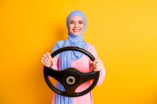 밝은 노란색 배경에서 격리된 보이지 않는 렌터카를 운전하는 히잡을 쓴 매력적인 콘텐츠 전문적인 쾌활한 이슬람 여성의 초상화