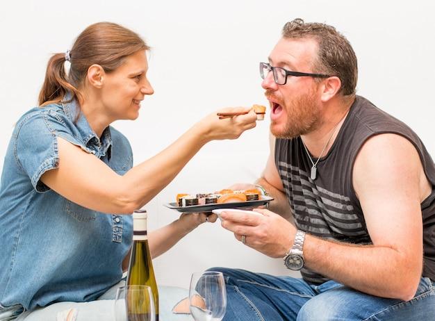 ソファで一緒に日本食を食べる魅力的なカップルの肖像画。スタイリッシュな家のインテリアでエキゾチックな食べ物を食べる家のソファでリラックスしたカップル