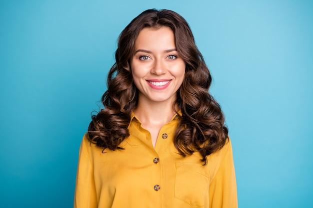 Портрет привлекательной кудрявой бизнес-леди, зубасто сияющей улыбкой, хорошее утро, настроение, готово начать работу, формальная одежда, желтая рубашка.