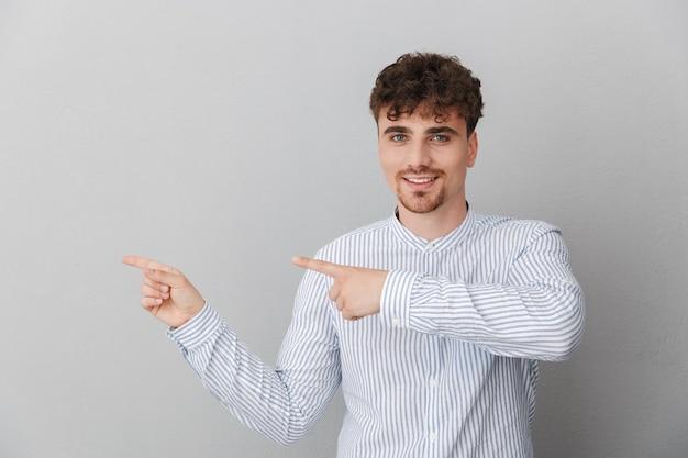 회색 벽에 격리된 카피스페이스에서 웃으면서 손가락을 옆으로 가리키는 셔츠를 입은 매력적인 곱슬머리 남자의 초상화