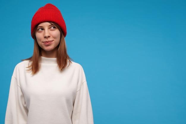 갈색 머리를 가진 매력적이 고 귀여운 여자의 초상화. 흰색 스웨터와 빨간 모자를 쓰고. 수줍게 웃고있다. 사람들이 개념. 파란색 벽 위에 고립 된 복사 공간에서 오른쪽으로 보는 꼬리 치는