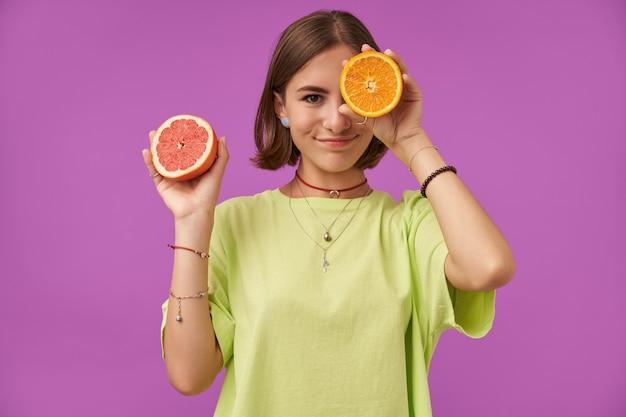 Портрет привлекательной, милой девушки с короткими волосами брюнетки. держа апельсин над глазом, закройте один глаз. стоя над фиолетовой стеной. ношение зеленой футболки, ожерелья, подтяжек и браслетов