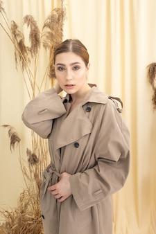 ドライフラワーとパステル生地の背景にベージュのレインコートで長い髪の魅力的なエレガントな白人の女の子の肖像画