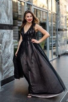 街の通り、夏の日にポーズをとってゴージャスな夜の黒のドレスで魅力的な女性モデルの肖像画