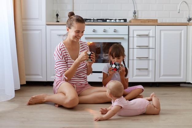 Портрет привлекательной женщины с запретом на волосы в полосатой повседневной рубашке, сидящей на полу на кухне с чашкой в руках, проводя время со своими маленькими дочерьми.