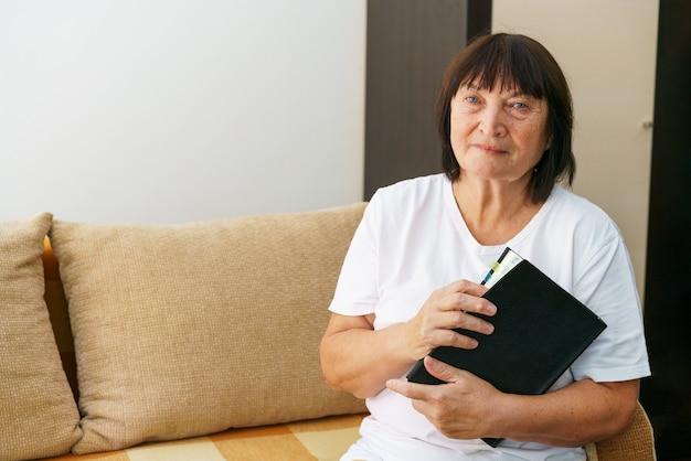 自宅で本の娯楽の夢を読んでソファに座っている魅力的な焦点を当てた陽気な女性の肖像画...