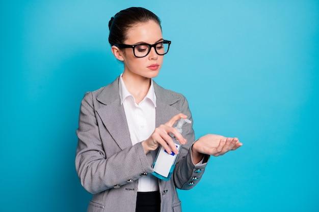 明るい青色の背景で隔離の手をきれいにするアルコール抗菌安全スプレー停止を使用して魅力的な焦点を当てた女性の肖像画