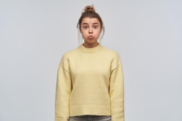 お団子に集まった金髪の魅力的で面白い女の子の肖像画。黄色いセーターを着ています。彼女の頬を吐き出します。感情の概念。白い壁に隔離されたカメラを見て