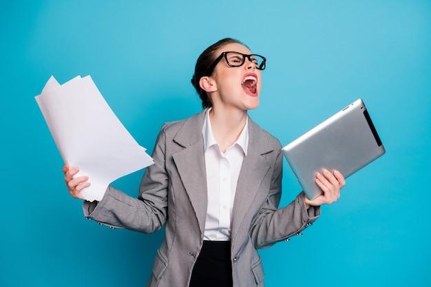 문서 비명을 관리하는 매력적인 분노의 미친 여성 전문가의 초상화는 밝은 파란색 배경에 격리되어 있습니다.